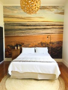 A beach mural makes a great accent wall and provides a headboard that takes up zero floor space.