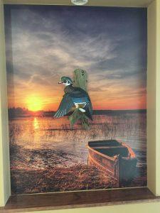 Lake Boat mural as backdrop for duck carving at Batesville Dental