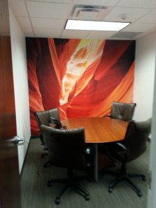 Even companies with the most open office plans have found it beneficial to outfit smaller conference rooms with equipment and backgrounds conducive to video conferencing. A professional background makes a much better impression on your customers than do the distractions that are often taking place in the background of group working locations. It's a lot quieter, too. Mural by Magic Murals.