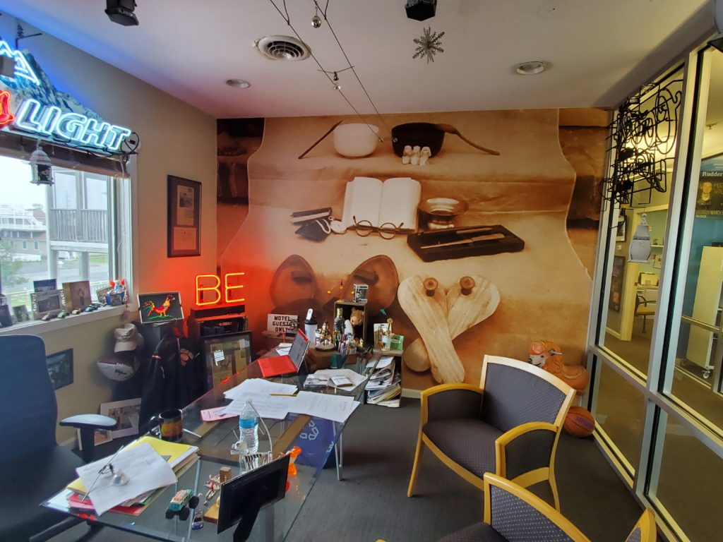 John Snow's office at restaurant and bar operator Highway One in Dewey Beach, DE has the perfect background for video conferences. Who wouldn't want to come to or perform at a restaurant or bar after they've seen the boss has such a cool office? Mural by Magic Murals.