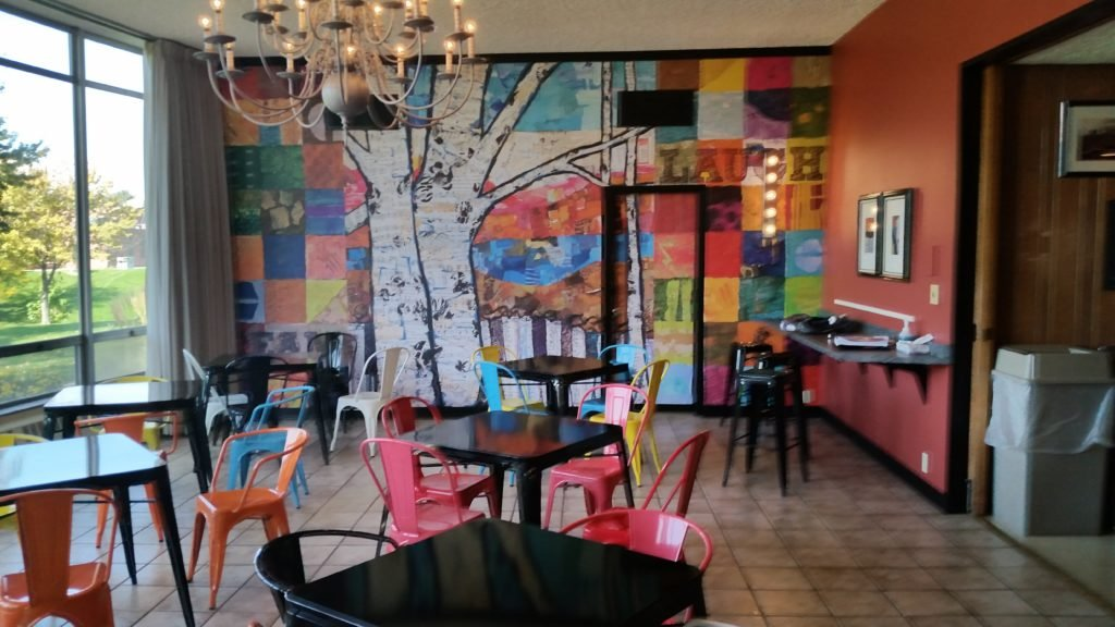 A really bright wall mural in this eclectic looking cafe makes it hard to resist going inside and hanging out for a fun time.