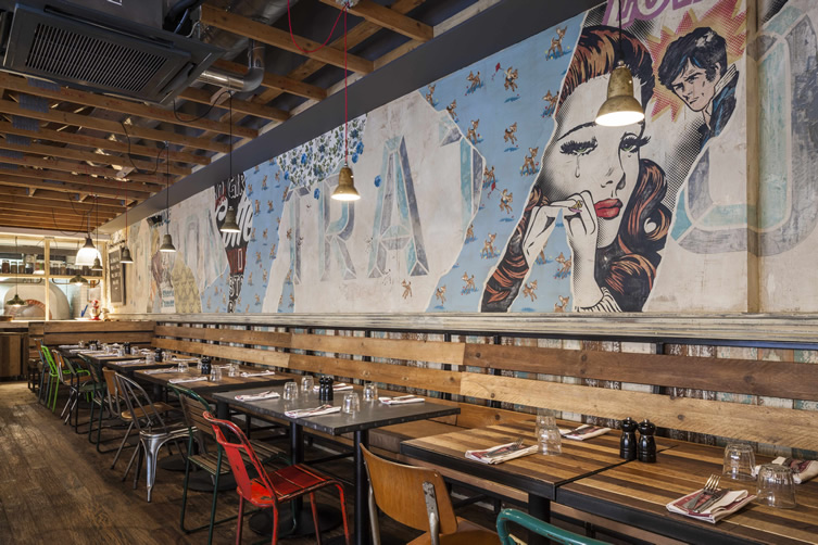 Celebrity chef Jamie Oliver's Trattoria in Surrey, England features a printed wallpaper mural designed by artists at Blacksheep Design.