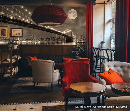Bright city lights of Manhattan and the Brooklyn Bridge compete with the full moon at night mural in sepia tone in a moody lounge style bar