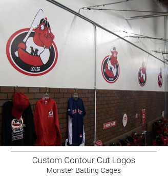 contour cut red and black monster themed graphics lining the wall in a batting cage