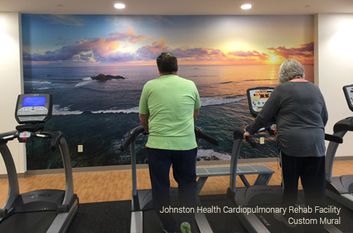 colorful shades of purple and blue and orange, sunrise/sunset over the ocean mural motivating walkers and runners in the treadmill section of the rehab facility