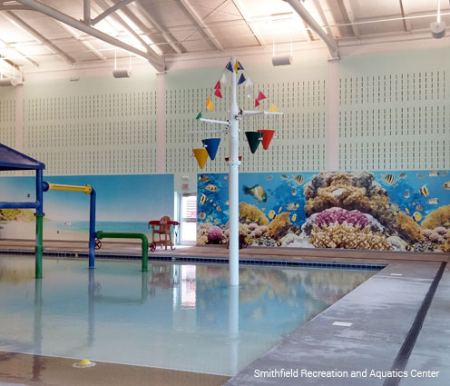 tropical beach and underwater coral reef with colorful fish murals lining aquatic center walls