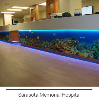 Sarasota Memorial Hospital's nurses station counter front mural wrap featuring underwater sea life, the colorful fish and reef, coral colors pop against the blue ocean floor highlight by the under counter lighting added by the hospital