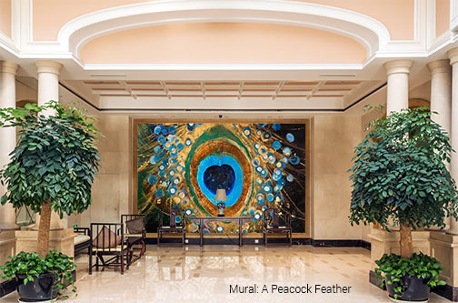 A colorful shades of blue and gold Peacock Feather wallpaper wall mural anchoring the lobby waiting area in an elegant hotel lobby