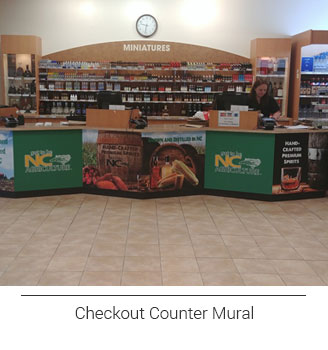 branded package store checkout counter front mural displaying North Carolina Department of Agriculture logos and scenery related to alcohol