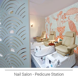 quirky and whimsical landscape artwork displaying whales, birds, plants in blue, white and orange hues flanking a wall in a nail salon behind the pedicure chairs