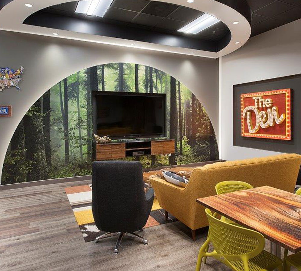 Customer project with green forest landscape mural in corporate lounge they decorated and name The Den