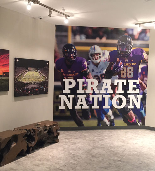 East Carolina University football Pirate Nation mural featured in a hallway, sitting area in a residential living complex